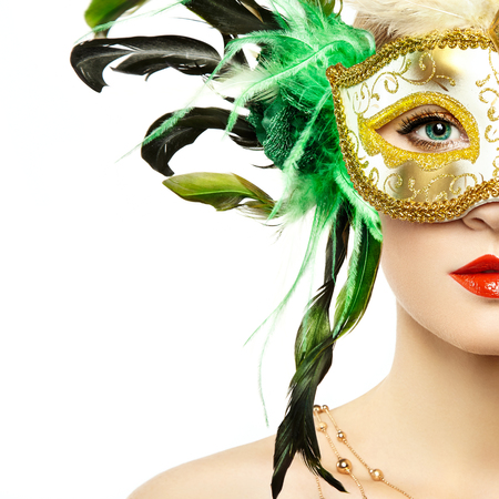Beautiful young Woman in Mysterious Golden Venetian Mask. Fashion photo. Masquerade Mask with Green Feathers