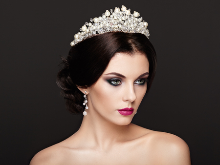 Fashion Portrait of Beautiful Woman with Tiara on head. Elegant Hairstyle. Perfect Make-Up and Jewelry. Red Lips 版權商用圖片