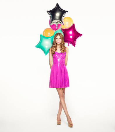 Beautiful young woman with colorful balloons on a white background. Birthday and party. Girl in pink dress at the festival. Valentine day Stock Photo