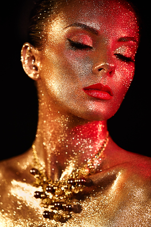 顔に輝きを放つ美人の肖像。カラーライトでアートメイクアップを持つ女の子。カラフルなメイクアップのファッションモデル 写真素材
