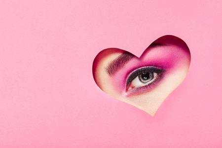 Fotografía conceptual del día de San Valentín. Ojo de niña con maquillaje rosa festivo. Corazón de papel sobre un fondo rosa. Símbolos de amor el día de San Valentín