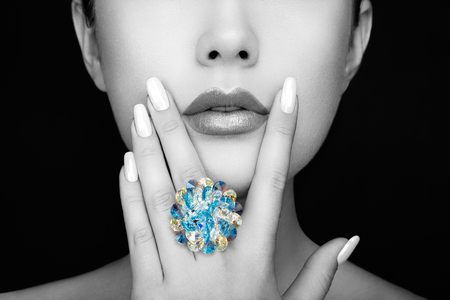 Beauty Fashion Woman lips with natural Makeup and white Nail polish. Gloss Lipstick. Beauty girl face close up. Sexy Lips, Manicure, Make up. Ring with Precious Stones, Jewelry