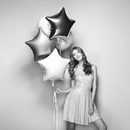 Beautiful Young Woman with Balloons on a White Background. Birthday and Party. Girl in Gray Dress at the festival. Black and White photo