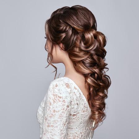Femme brune aux cheveux bouclés longs et brillants. Belle mannequin avec une coiffure frisée. Soin et Beauté Produits capillaires. Soin et beauté des cheveux