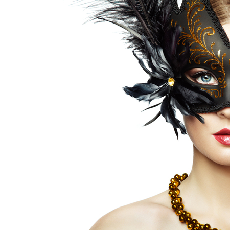 Beautiful young Woman in Mysterious Black Venetian Mask. Fashion photo. Masquerade Mask with Black Feathers Standard-Bild