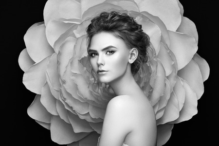 Beautiful woman on the background of a large flower. Beauty summer model girl with peony. Young woman with elegant hairstyle and makeup. Fashion photo 版權商用圖片