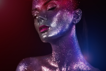 Portrait of Beautiful Woman with Sparkles on her Face. Girl with Art Make-Up in Color Light. Fashion Model with Colorful Makeup