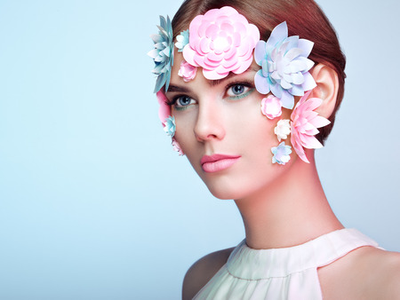 Face of Beautiful Woman Decorated with Flowers. Perfect Makeup. Beauty Fashion Model Woman Face perfect Skin. Paper Flowers Stock Photo