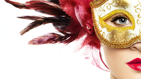 Beautiful young Woman in Mysterious Golden Venetian Mask. Fashion photo. Masquerade Mask with Red Feathers