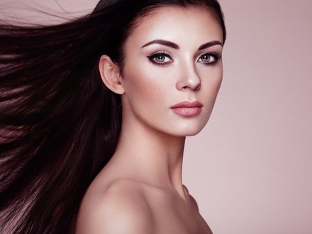 Beautiful Woman with Long Smooth Hair. Girl with Perfect Makeup and Hairstyle. Model Brunette with Perfect Healthy dark Hair. Care and Hair Products