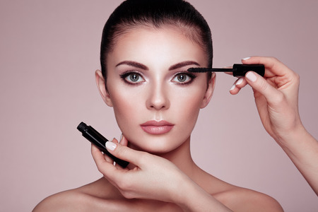Beautiful Brunette Woman Paints the Eyelashes. Beautiful Woman Face. Makeup Detail. Beauty Girl with Perfect Skin. Make Up in process. Makeup Artis