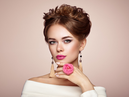 Brunette Woman with Elegant and shiny Hairstyle. Beautiful Model Woman with Curly Hairstyle. Care and Beauty Hair products. Perfect Make-Up. Nails and Manicure