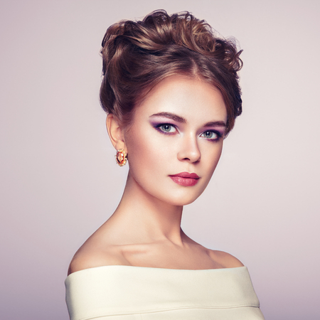 Brunette Woman with Elegant and shiny Hairstyle. Beautiful Model Woman with Curly Hairstyle. Care and Beauty Hair products. Perfect Make-Up