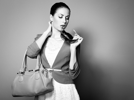 Portrait of beautiful young woman with a leather bag. Fashion photo 写真素材