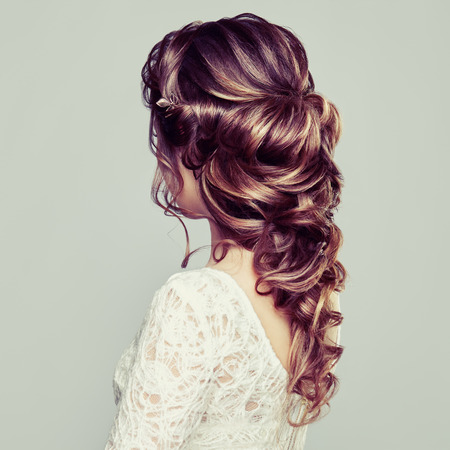 Brunette Woman with Long and shiny Curly Hair. Beautiful Model Lady with Curly Hairstyle. Care and Beauty Hair products. Care and Beauty of Hair Stock Photo