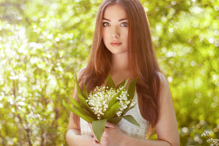 Portrait of beautiful young woman with lily of the valley. Girl on nature. Spring flowers. Fashion beauty Banco de Imagens