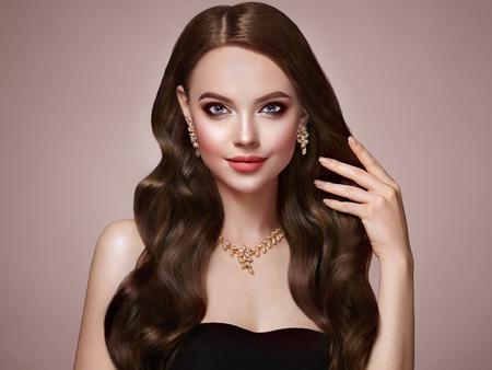 Brünettes Mädchen mit langen gesunden und glänzenden lockigen Haaren. Pflege und Schönheit. Schöne vorbildliche Frau mit gewellter Frisur. Make-up und Schmuck