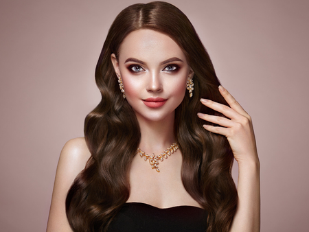 Brunette Girl with Long Healthy and Shiny Curly Hair. Care and Beauty. Beautiful Model Woman with Wavy Hairstyle. Make-Up and Jewelry
