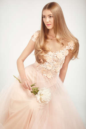 Beautiful Woman in Lace Wedding Dress. Beautiful Lady with Healthy and Beauty Hair. Woman with a peony Stok Fotoğraf