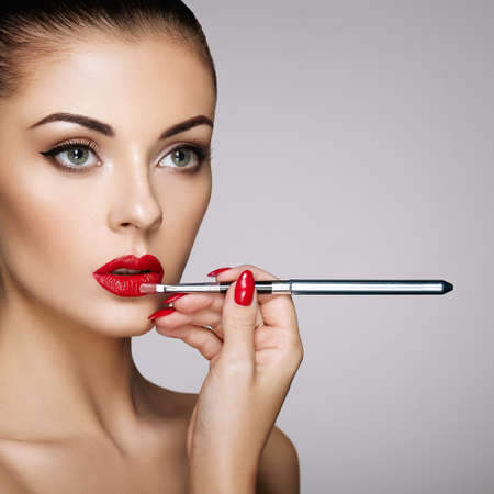 Beautiful Woman paints Lips with Lipstick. Beautiful Woman Face. Makeup detail. Beauty Model with Perfect Skin. Red Lips and Nails Manicure Stok Fotoğraf