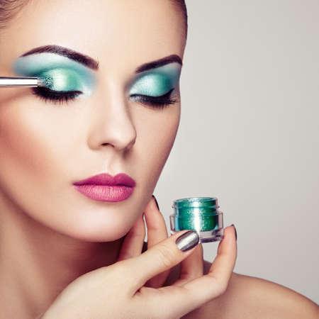 Make-upartiest past oogschaduw toe. Mooie vrouw gezicht. Perfecte make-up. Make-up detail. Schoonheid meisje met perfecte huid. Nagels en manicure Stockfoto