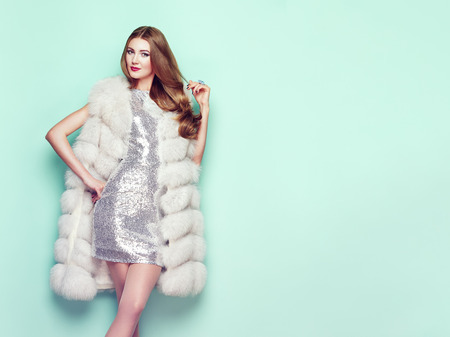 Fashion Portrait Young Woman in white Fur Coat. Girl with Elegant Hairstyle Posing on a Colored Background. Lady Posing in Eco-Fur Coat. Beautiful Luxury Winter Woman. Fashion Model in Silver Dress