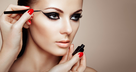 Makeup Artist Applies Eyeshadow. Beautiful Woman Make-up Eye with Black Liner. Fashion Makeup Arrows. Red Nails Perfect Skin