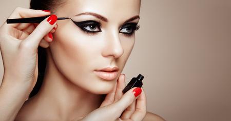 Maquilleur applique le fard à paupières. Belle femme maquillage yeux avec doublure noire. Flèches de maquillage de mode. Ongles Rouges Perfect Skin