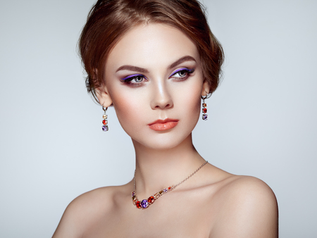 Portrait Beautiful Woman with Jewelry. Fashion Makeup and Cosmetics. Elegant Hairstyle. Violet Make-up Arrows. Beauty and Accessories Stok Fotoğraf