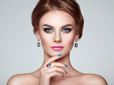 Portrait Beautiful Woman with Jewelry. Model Girl with Blue Manicure on Nails. Elegant Hairstyle. Blue Make-up Arrows. Beauty and Accessories Stock Photo
