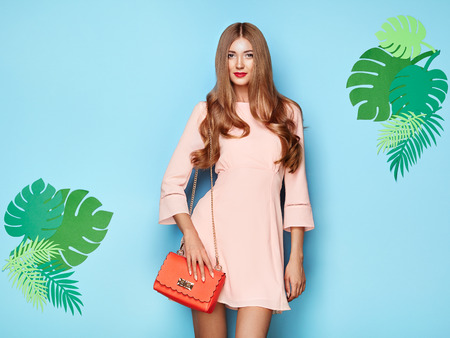 Portrait of Fashion Young woman in Pink Dress. Lady in Stylish Summer Outfit. Girl Posing on a Blue Background. Stylish Hairstyle. Model On the background of Tropical Leaves Imagens - 109259338