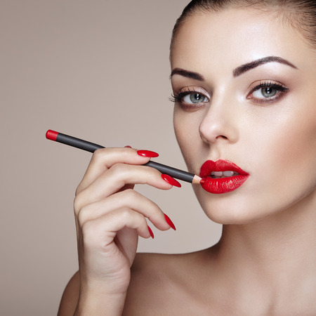 Beautiful woman paints lips with lipstick. Beautiful woman face. Makeup detail. Beauty girl with perfect skin Stok Fotoğraf