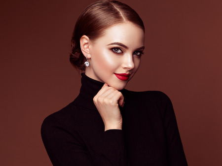 Beautiful Young Woman with Clean Fresh Skin. Perfect Makeup. Beauty Fashion. Red Lips. Cosmetic Eyeshadow. Smooth Hair. Girl in Black Turtleneck Фото со стока