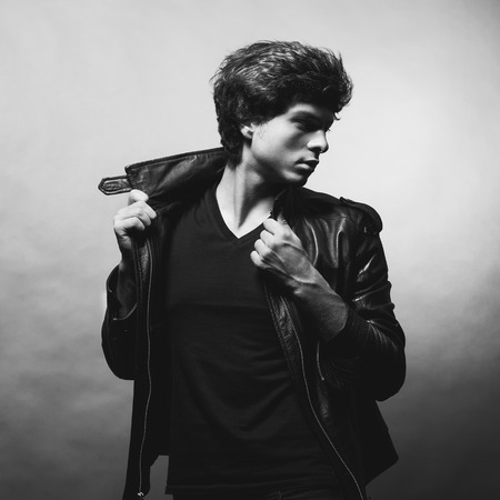 Portrait of Handsome Young Man. A Men in a Leather Jacket posing on a Gray Background. Black And White Photo
