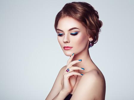 Portrait belle femme avec des bijoux. Fille modèle avec manucure bleue sur les ongles. Coiffure élégante. Flèches de maquillage bleues. Beauté et accessoires