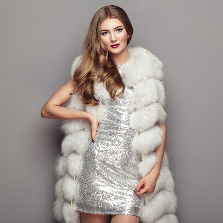 Fashion Portrait Young Woman in white Fur Coat. Girl with Elegant Hairstyle Posing on a Gray Background. Lady Posing in Eco-Fur Coat. Beautiful Luxury Winter Woman. Fashion Model in Silver Dress