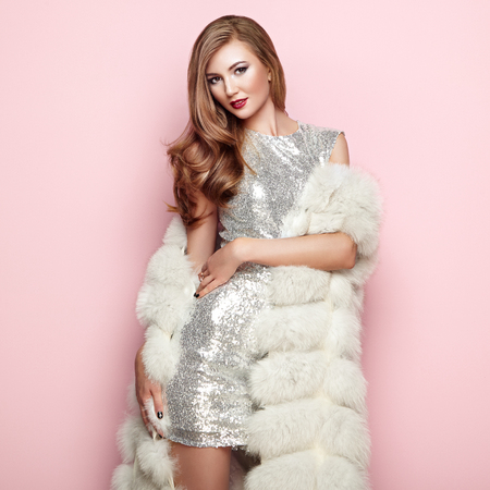 Fashion Portrait Young Woman in white Fur Coat. Girl with Elegant Hairstyle Posing on a Pink Background. Lady Posing in Eco-Fur Coat. Beautiful Luxury Winter Woman. Fashion Model in Silver Dress