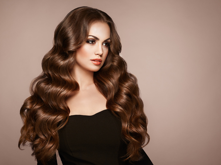 Fille brune aux longs cheveux bouclés sains et brillants. Soins et beauté. Belle femme modèle avec une coiffure ondulée. Maquillage et robe noire