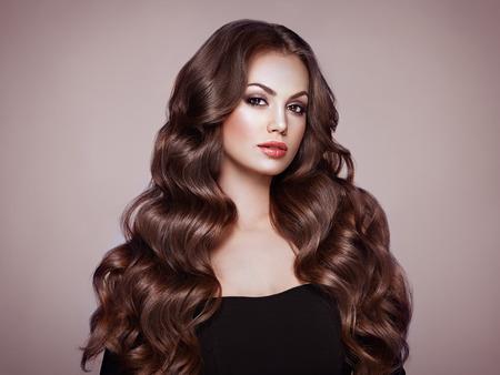 Brünettes Mädchen mit langen gesunden und glänzenden lockigen Haaren. Pflege und Schönheit. Schöne vorbildliche Frau mit gewellter Frisur. Make-up und schwarzes Kleid