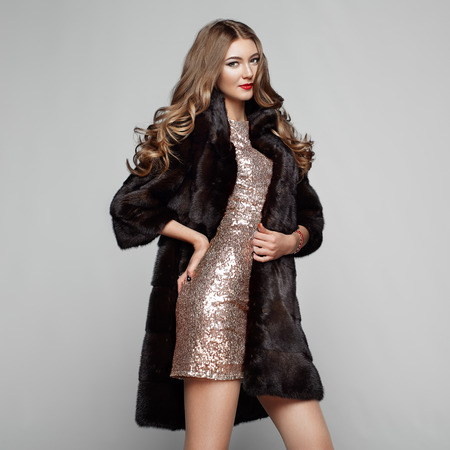 Fashion Portrait Young Woman in Black Fur Coat. Girl with Elegant Hairstyle Posing on a Gray Background. Lady Posing in Eco-Fur Coat. Beautiful Luxury Winter Woman. Fashion Model in Golden Dress