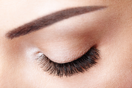 Female Eye with Extreme Long False Eyelashes. Eyelash Extensions. Makeup, Cosmetics, Beauty. Close up, Macro Banco de Imagens