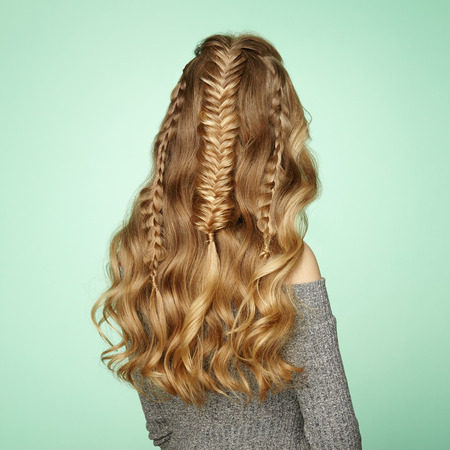 Blonde Girl with Long and Shiny Curly Hair. Beautiful Model Woman with Curly Hairstyle. Care and Beauty Hair Products. Lady with braided hair Stock Photo
