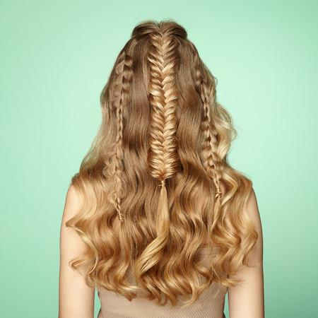 Blondes Mädchen mit langem und glänzendem lockigem Haar. Schöne vorbildliche Frau mit lockiger Frisur. Pflege- und Schönheitshaarprodukte. Dame mit geflochtenem Haar