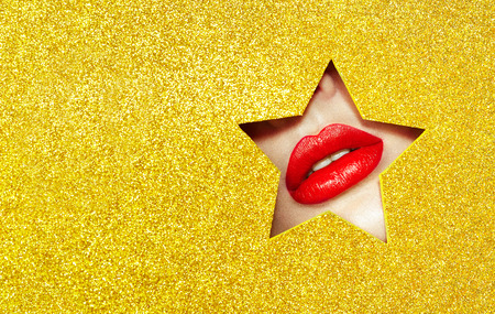 Beautiful Plump Bright Lips Of a Young Beautiful Woman with Red Lipstick Look Into the Pattern of Star made of Colored Paper. Yellow. Holiday Patterns. Golden Paper Stock Photo