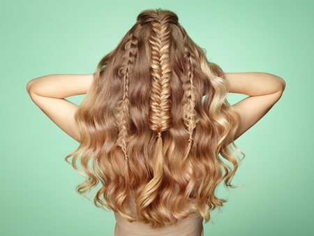 Blonde Girl with Long and Shiny Curly Hair. Beautiful Model Woman with Curly Hairstyle. Care and Beauty Hair Products. Lady with braided hair Standard-Bild