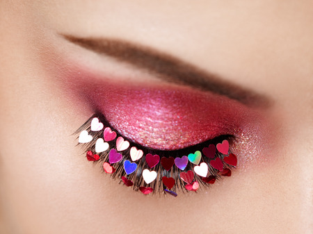 Eye Make-up Girl with a Heart. Valentine's Day Makeup. Beauty Fashion. Eyelashes. Cosmetic Eyeshadow. Makeup Detail. Female Eye with Extreme Long False Eyelashes