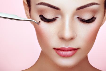 Schöne Frau mit extrem langen falschen Wimpern. Wimpernverlängerungen. Make-up, Kosmetik. Schönheit, Hautpflege. Frau klebt Wimpern Standard-Bild