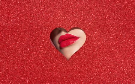 Beautiful Plump Bright Lips Of a Young Beautiful Woman with Red Lipstick Look Into the Pattern of Heart Shaped made of Colored Paper. Holiday Patterns. Valentine's Day. Beautiful Love Make-up Banque d'images - 117127732