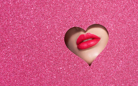 Beautiful Plump Bright Lips Of a Young Beautiful Woman with Red Lipstick Look Into the Pattern of Heart Shaped made of Colored Paper. Holiday Patterns. Valentines Day. Beautiful Love Make-up 写真素材