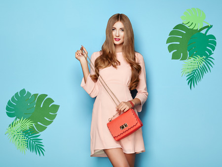 Portrait of Fashion Young woman in Pink Dress. Lady in Stylish Summer Outfit. Girl Posing on a Blue Background. Stylish Hairstyle. Model On the background of Tropical Leaves